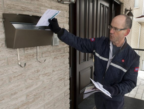 Letter carrier Richard Autotte delivers mail in the east end of Montreal Thursday, March 5, 2015. Police are investigating a series of robberies on letter carriers by thieves who have been taking the carriers keys to community and apartment mailboxes. THE CANADIAN PRESS/Ryan Remiorz