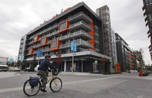 A cyclist rides through the Millennium Water development which was the athletes' village during the 2010 Winter Olympics in Vancouver, B.C., on October 7, 2010. What threatened to be an Olympic-sized white elephant for the City of Vancouver has instead become a valuable asset. The city has sold its remaining interest in 67 condominium units in the Olympic Village development for $91 million to the Aquilini Group, the owner of the Vancouver Canucks hockey team. Photograph by: DARRYL DYCK , THE CANADIAN PRESS