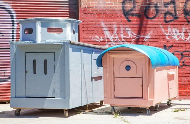 two colorfully painted structures made by the homeless homes project