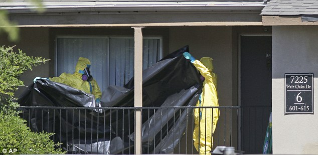 Hazardous material cleaners prepare to hang black plastic outside the apartment in Dallas today where Thomas Eric Duncan, the Ebola patient who traveled from Liberia to Dallas, stayed last week. The family living there has been confined under armed guard while being monitored by health officials for Ebola symptoms Read more: http://www.dailymail.co.uk/news/article-2780209/Ordeal-Dallas-Ebola-apartment-comes-end-Quarantined-family-moved-secret-location-Hazmat-team-arrived-FIVE-DAYS-victim-diagnozed.html#ixzz3FNfvlNQE